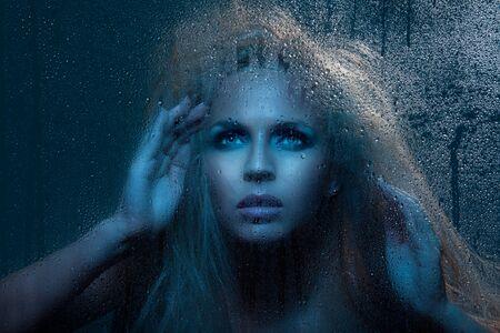 Beautiful woman looking through night window with rain outside Stock Photo - 10315119