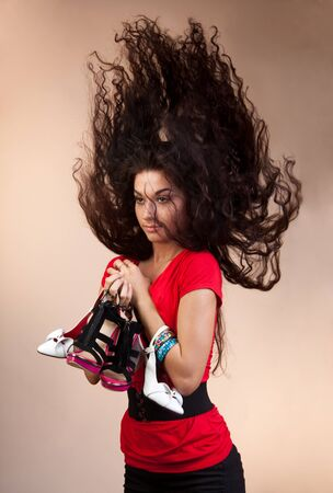 Beautiful girl holding many shoes of different kind and her hair flying up photo