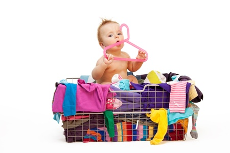 Baby in basket with clothes with hanger, isolated on white photo