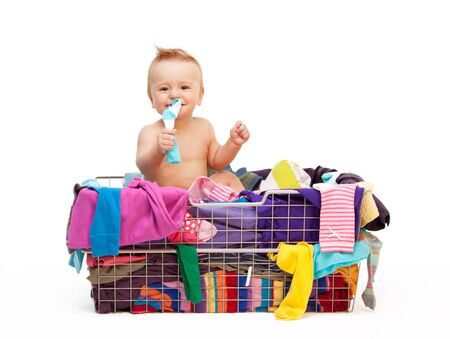 baby wardrobe: Happy toddler sitting  in basket with clothes Stock Photo
