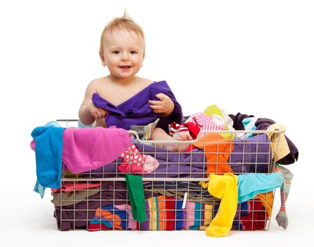 kids wear: Happy smiling toddler in big basket with clothes