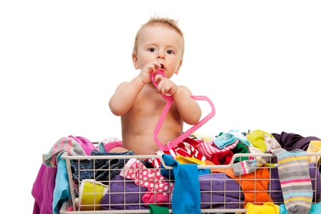 clean clothes: Toddler sitting in basket with clothes and holding hanger