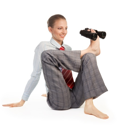 Business woman sitting in flexible pose and holding binoculars with her leg describing precise forecast concept photo