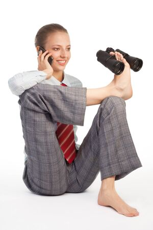 Business woman sitting in flexible pose and holding binoculars and speaking by cell phone Stock Photo - 10832722