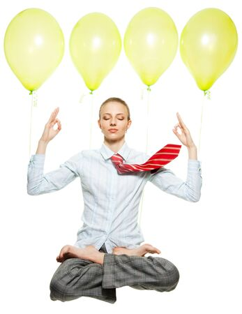 business woman sitting in lotus pose and flying on air balloons, meditating, with flying tie photo