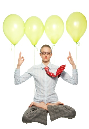 business woman sitting in lotus yoga pose and flying on air balloons, meditating, with flying tie photo