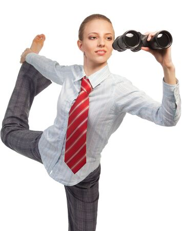 Business woman standing in flexible pose and looking in binocular researching field photo