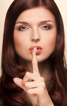 Close-up beauty portrait of woman showing silence sign and looking at camera photo