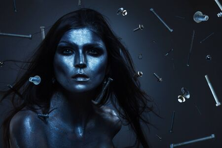 terminator: Creative shoot of woman with  metal color paint on face and many screws flying around Stock Photo