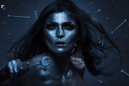 Creative shoot of woman with screwdriver and many screws flying around, metal color paint on face photo
