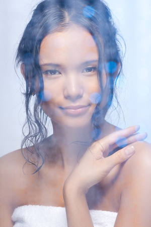 Nice Asian woman in the bathroom behind the frosted glass with wet curly hair photo