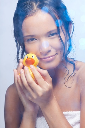 Beautiful happy Asian woman in bathroom playing with duckling photo
