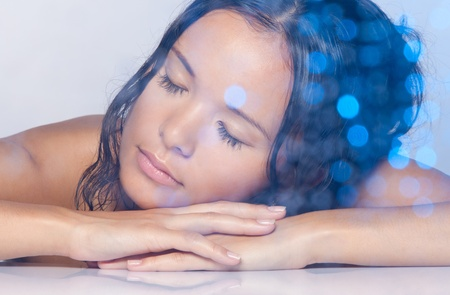 Calm relaxed Asian girl with wet hair laying with closed eyes photo