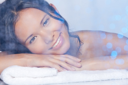 Beauty portrait of a woman in the bath laying on the towel and smiling photo