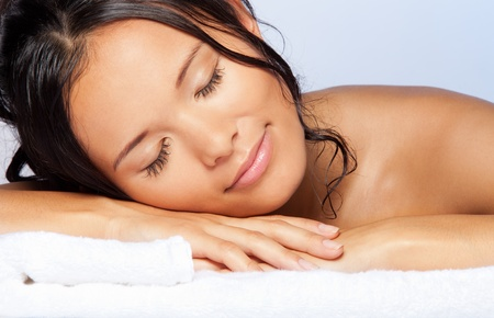 Sleeping and enjoying young Asian girl laying on the towel and smiling with wet hairs - close-up portrait photo