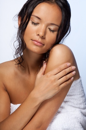 Smiling Asian girl wrapped in towel, after bath with wet hairs photo