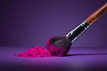 makeup a brush: Clouse-up of makeup brush and face powder on purple background