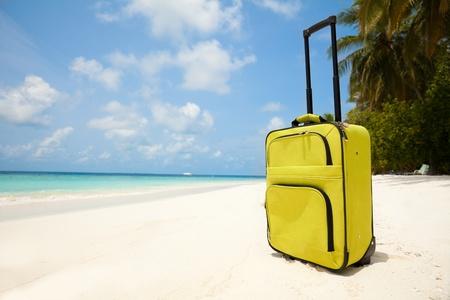 maletas de viaje: Maleta en la playa con arena blanca, cielo, sol y palmeras que representan conceptos de viajes de vacaciones
