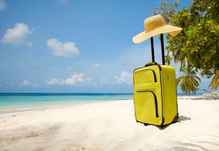 maletas de viaje: Maleta y el gran sombrero de paja en la playa Foto de archivo