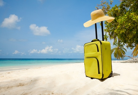 summer wear: Suitcase and big straw hat on the beautiful beach