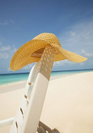 deck chair: Straw hat hanging on the deck chair with beach on the background