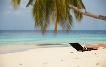 Tropical beach background and laptop on the sand with hands typing photo