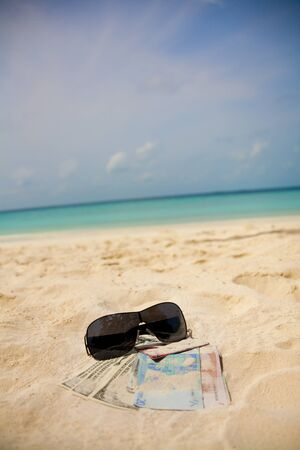Money, credit card and shades on the beach sand photo
