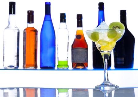 botella de licor: Cóctel de cristal con bebida con botellas en el fondo de la barra blanca Foto de archivo