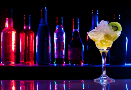 Cocktail drink with colorful light on background bottles photo