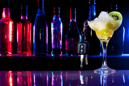 Alcohol drink in cocktail glass and car keys hanging from it photo