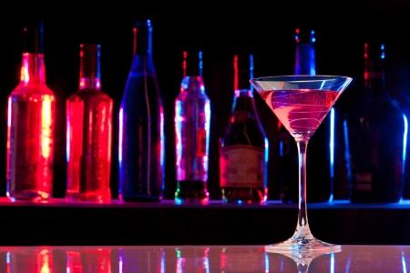 botella de licor: Cóctel de cristal con bebida en el bar con botellas en el fondo oscuro Foto de archivo