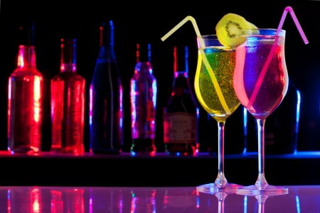liquor bottle: Two pink and yellow cocktails in the glass with straw and kiwi, and bar bottles row on the background
