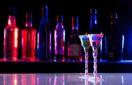 botella de licor: Dos pequeños vasos con bebida de alcohol en la barra con una fila de botellas en el fondo