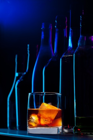 Close-up of whiskey drink and bottles standing on the bar photo