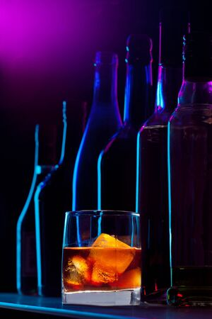 Alcohol drink with ice and silhouette of the different bottles on dark background photo