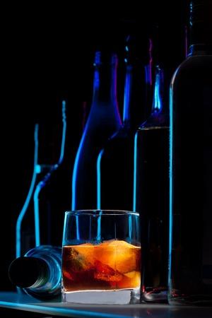botella de licor: el whisky con hielo y siluetas de botellas en el fondo oscuro bar