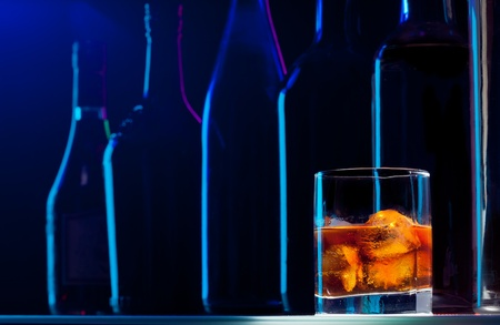 Whiskey with ice in the good bar, with light making beautiful silhouettes of bottles on the background photo