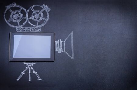 tripod: Tablet computer as movie camera on the blackboard with tripod and strobe drawn with chalk