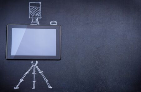 Tablet computer as photo camera on the blackboard with tripod and strobe drawn with chalk photo
