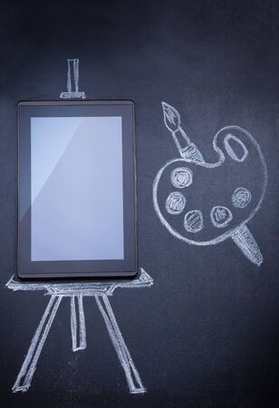 Tablet computer as easel for painting with paint brush on the blackboard with tripod and strobe drawn with chalk photo
