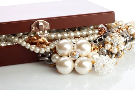 Wooded bow with jewelry and pearl necklace inside and slightly open cover photo