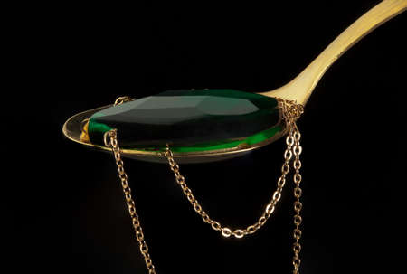 coulomb: Golden spoon with coulomb from green stone and chain Stock Photo