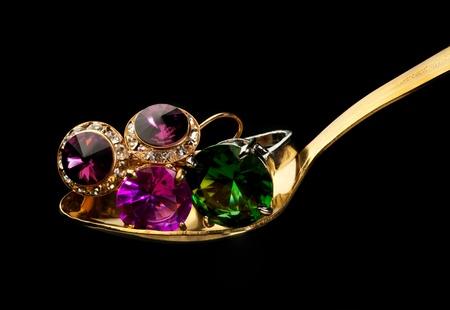 Gouden lepel met sieraden zoals ringen met stenen en ringen Stockfoto