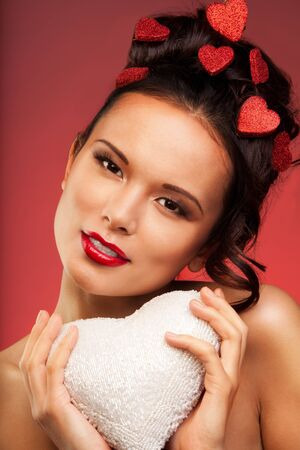 Beauty shoot of a woman holding white heart made of beads and hairstyle with hearts and exressing love photo