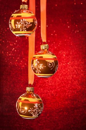 Three Christmas balls on red sparkling background photo