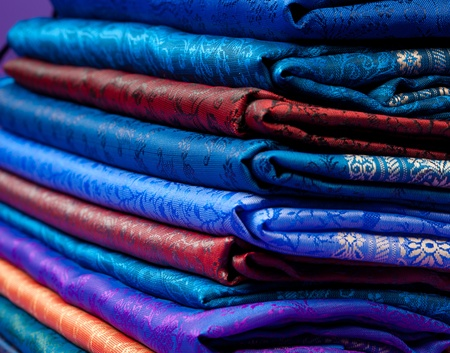 indian fabric: Beautiful silk of different colors and ornament Indian fabric laying in pile Stock Photo