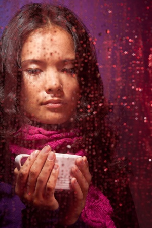Thoughtful and a bit sad Asian woman in rainy weather with cup of hot tea behind the glass photo