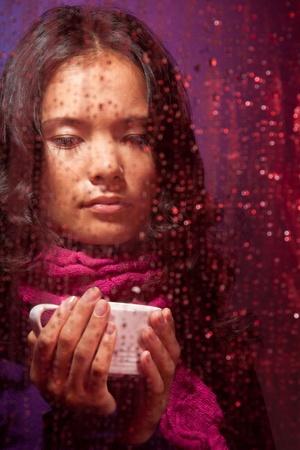 Zamyślony i nieco smutna kobieta Azji w deszczową pogodę z filiżanką gorącej herbaty za szybą