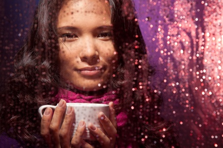 Positive Asian woman behind the glass in rainy weather with cup of hot tea photo