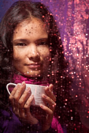 Positive Asian woman behind the glass in cold rainy weather with cup of hot tea photo